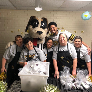 Saints player and mascot with kitchen staff