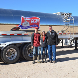 family in front of a tanker of milk