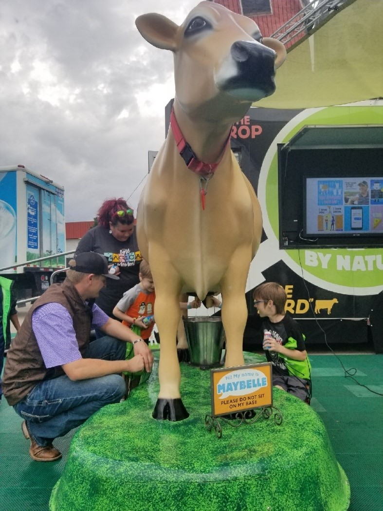 dairy farmer helping a student milk a model cow