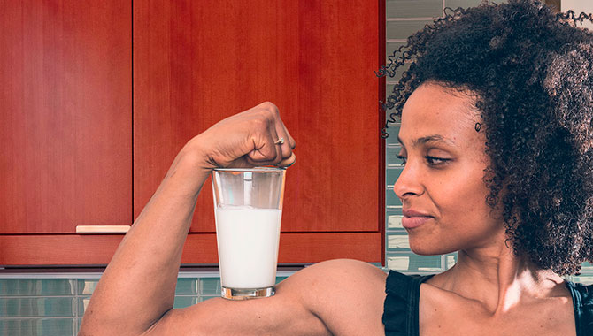 woman flexing with a glass of milk on her bicep