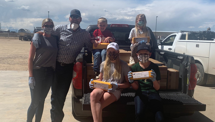 The Diepersloot family, all wearing cloth masks, in their truck with some of the cheese they donated