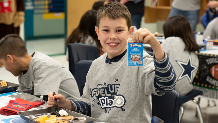 young boy drinks chocolate milk with his school breakfast in a fuel up to play 60 t shirt