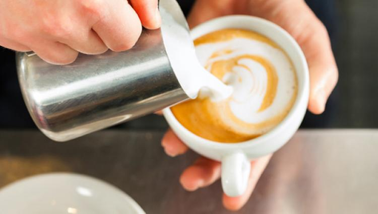 person pouring a latte