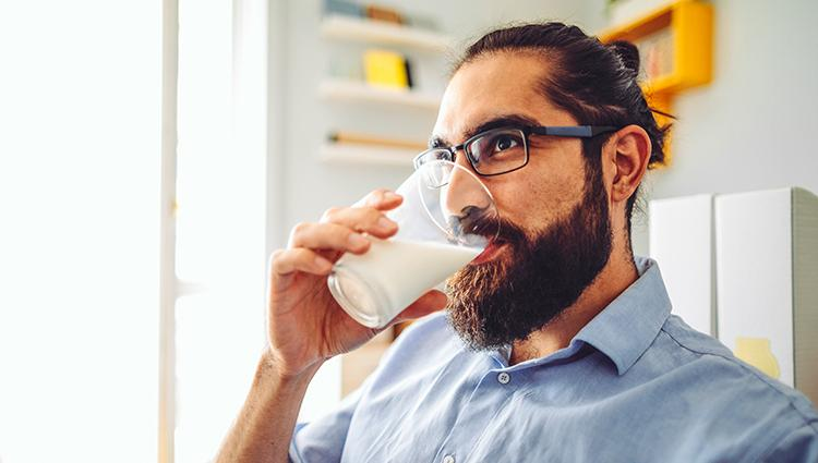 person with a beard drinking milk