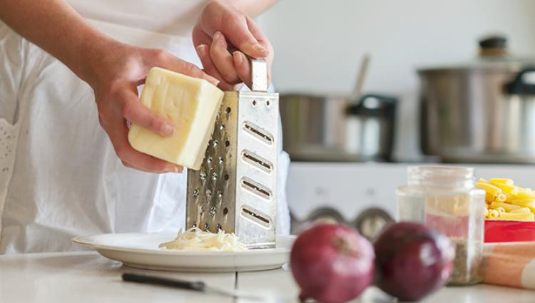 grating a piece of white cheese