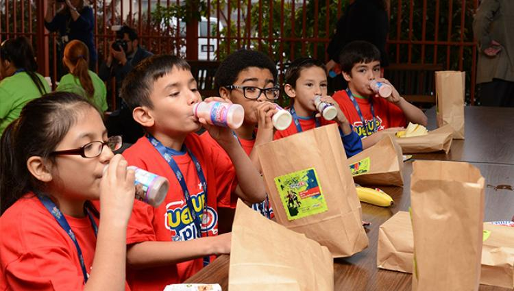 kids drinking milk with sack lunches