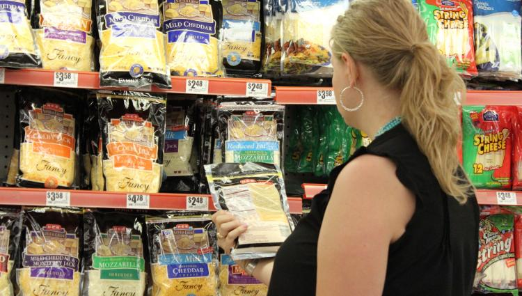 woman looking at cheese at the grocery store
