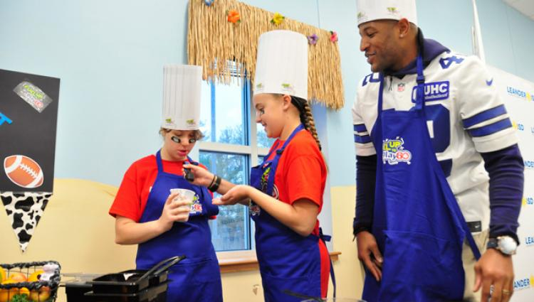 kids in aprons cooking with a Dallas Cowboy