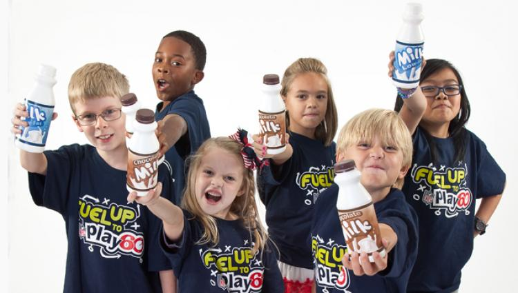 group of kids in fuel up to play 60 shirts toasting with milk
