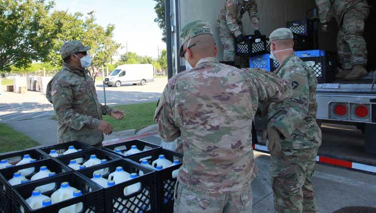 national guard members help load up gallons of milk on a truck