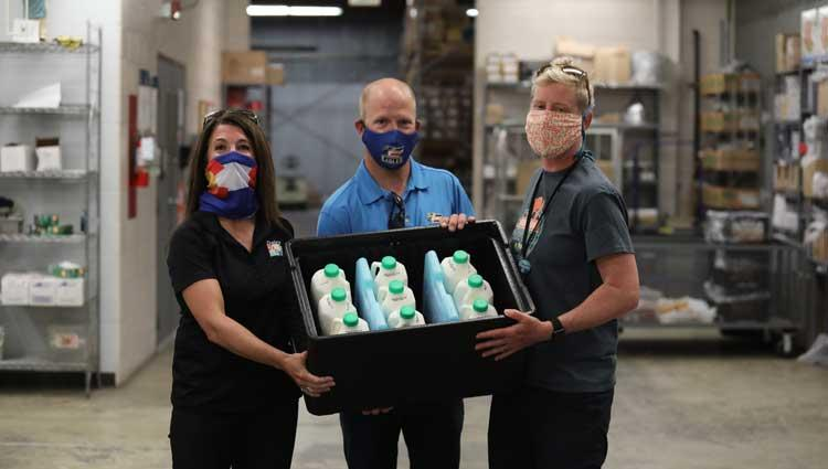 3 people holding a cooler full of milk