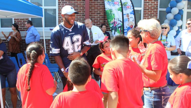 Dallas cowboy speaking with a group of students