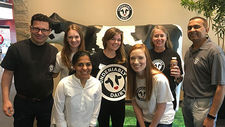 group of people with a large cow sculpture and Undeniably Dairy logo