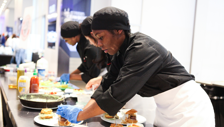 young person preparing food in an apron and chef's hat