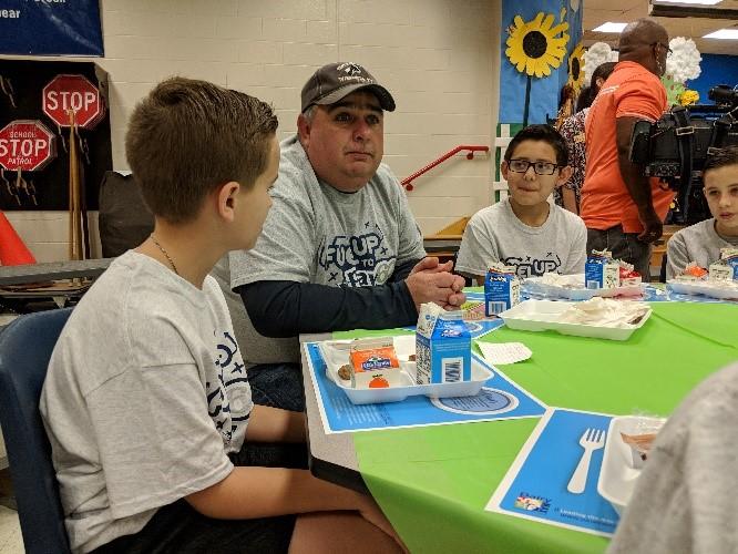 dairy farmer Mark Sustaire eats school breakfast with 2 students